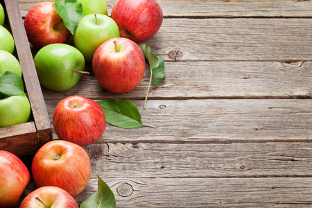 Ripe green and red apples on wooden table. With space for your text