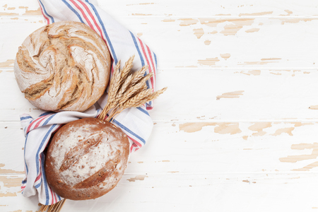 Various crusty bread on white wooden table. Top view with space for your text Stockfoto