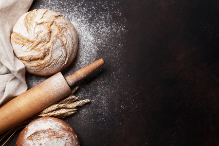 Homemade crusty bread cooking on stone table. Top view with space for your text
