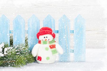 Christmas snowman toy, decor and fir tree branch. Xmas greeting card Фото со стока