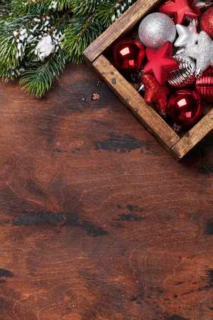 Christmas decor and fir tree branch covered by snow on wooden background. Top view xmas backdrop with space for your greetings
