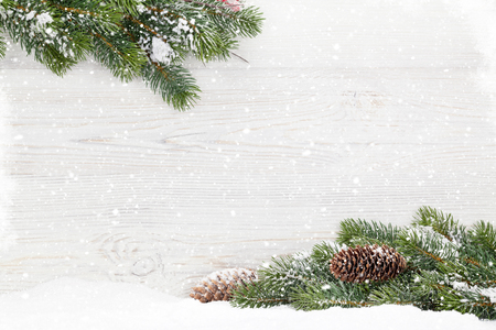 Christmas fir tree branch covered by snow on wooden background. Top view xmas backdrop with space for your greetings