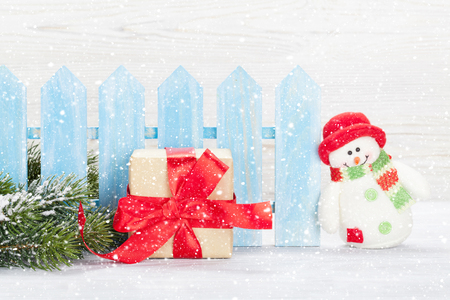 Christmas snowman toy, gift box and fir tree branch. Xmas greeting card with space for your greetings