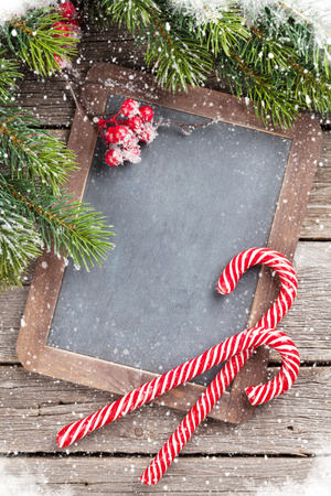 Christmas candy cane and snow fir tree on wooden table. Top view with chalkboard for your greetings Stockfoto