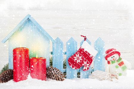 Christmas snowman, mitten, sledge toys, candles and fir tree branch. Xmas backdrop with copy space