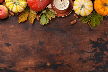 Autumn backdrop with pumpkins, coffee and colorful leaves on wooden background. Top view with space for your text Stock Photo