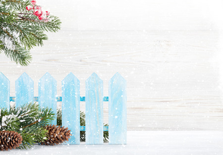 Christmas fir tree branch covered by snow on wooden background. Xmas card backdrop with space for your greetings
