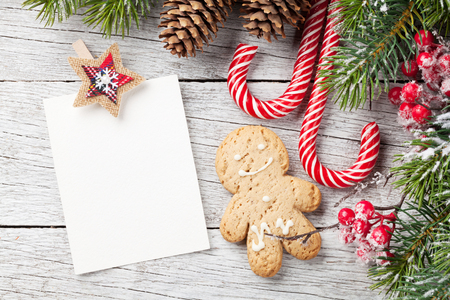 Christmas blank photo frame, gingerbread cookie and snow fir tree on wooden table. Top view with space for your greetings