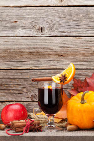 Autumn still life with mulled wine, pumpkins, apples, pears and colorful leaves in front of wooden wall. With space for your text