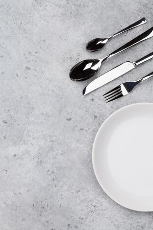 Tafel opstelling. Leeg bord, mes, vork en lepels. Bovenaanzicht en plat leggen met kopie ruimte Stockfoto