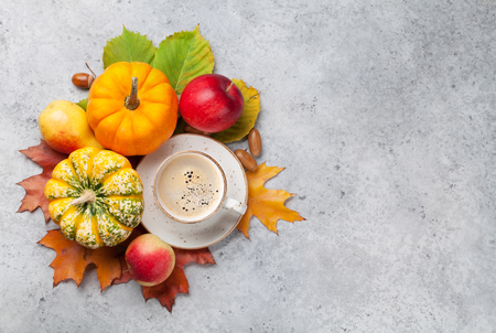 Autumn backdrop with pumpkins, apples, pears, coffee and colorful leaves over stone background. Top view with space for your text Stock Photo