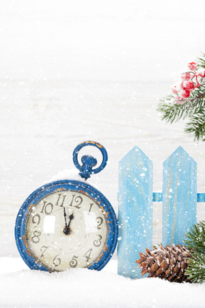 Christmas alarm clock and fir tree branch covered by snow in front of wooden wall. With copy space for your greetings Фото со стока