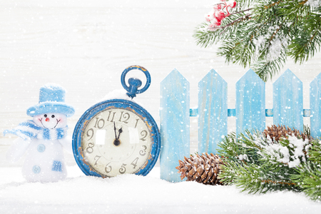 Christmas snowman toy, alarm clock and fir tree branch covered by snow in front of wooden wall. With copy space for your greetings