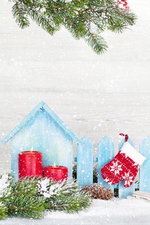 Christmas candles, decor and fir tree branch covered by snow in front of wooden wall. View with copy space Фото со стока