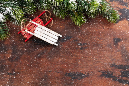 Christmas backdrop with decor and fir tree branch covered by snow oves wooden texture. Xmas background with space for your greetings 版權商用圖片 - 110344080