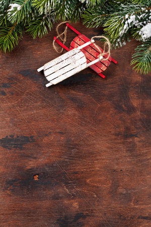 Christmas backdrop with decor and fir tree branch covered by snow oves wooden texture. Xmas background with space for your greetings Reklamní fotografie - 110344059