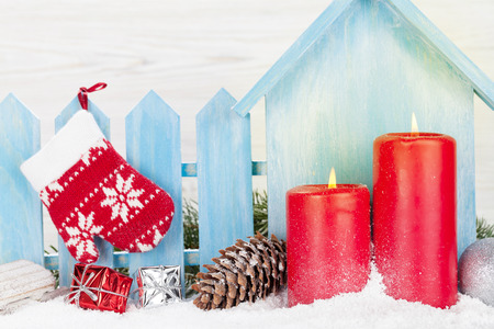 Christmas candles, decor and fir tree branch covered by snow in front of wooden wall. View with copy space 版權商用圖片