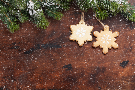 Christmas gingerbread cookies and xmas fir tree branch over wooden backdrop. Top view with space for your greetings