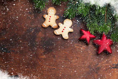 Christmas gingerbread cookies, decor and xmas fir tree branch over wooden backdrop. Top view with space for your greetings
