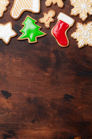 Christmas gingerbread cookies over wooden backdrop. Top view with space for your greetings