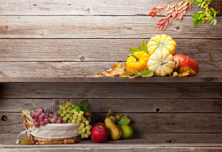 Autumn still life with pumpkins, apples, pears, grapes and colorful leaves. With space for your text