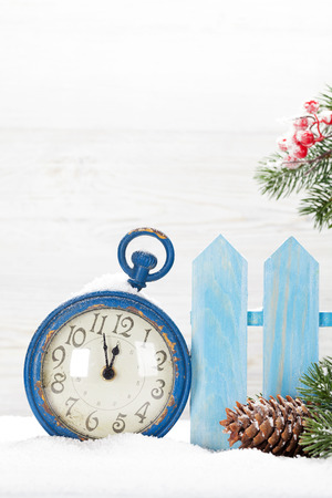 Christmas alarm clock and fir tree branch covered by snow in front of wooden wall. With copy space for your greetings Stock Photo