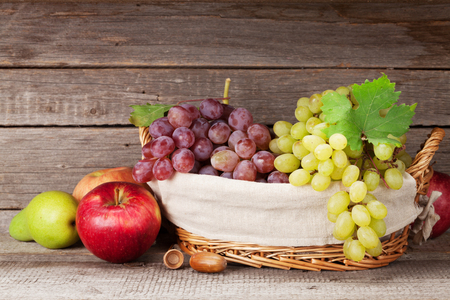 Autumn still life with apples, pears, grapes and colorful leaves. With space for your text Stock Photo