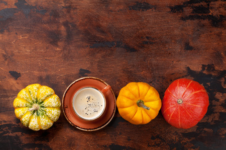 Autumn still life with pumpkins, coffee over wooden background. Top view with space for your text
