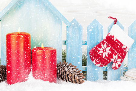 Christmas decor, candles and fir tree branch covered by snow in front of wooden wall. Xmas greeting card