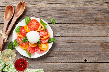 Caprese salad with tomatoes, basil and mozzarella. With rose and white wine. Top view with space for your text Stock Photo