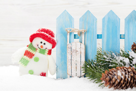 Christmas snowman and sledge toys, gift box and fir tree branch