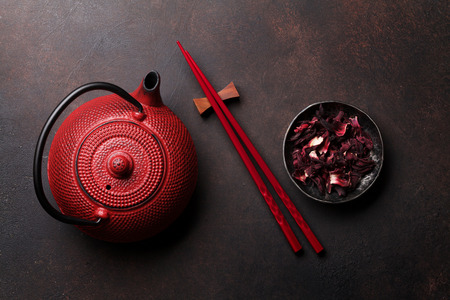 Red teapot, dry tea and sushi chopsticks. Top view