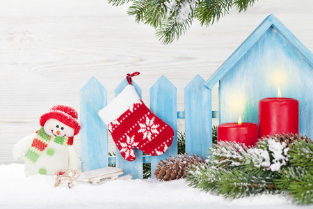 Christmas candles, snowman toy, decor and fir tree branch. Xmas greeting card with space for your greetings Stockfoto