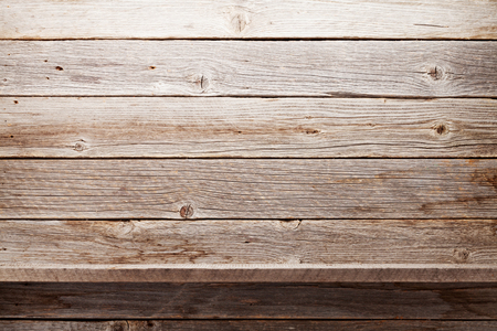 Empty wooden shelve in front of wooden wall with copy space