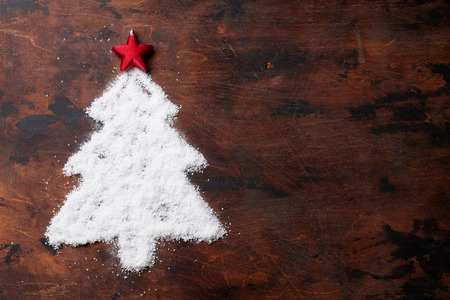 Christmas fir tree shaped snow and star decor over wooden backdrop greeting card. Top view with space for your greetings