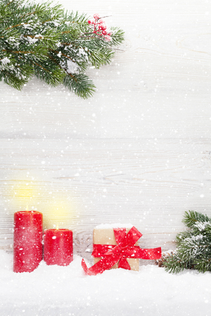 Christmas gift box, candles and fir tree branch covered by snow in front of wooden wall. Xmas backdrop with space for your greetings