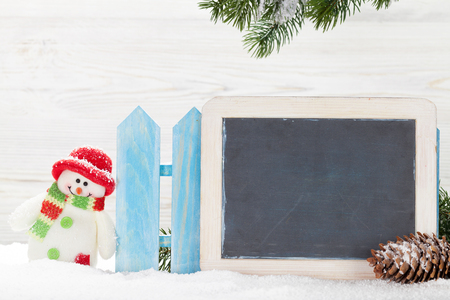 Christmas snowman toy and xmas fir tree branch. With chalkboard for your greetings