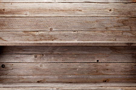 Empty wooden shelves in front of wooden wall with copy space
