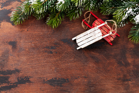 Christmas backdrop with decor and fir tree branch covered by snow oves wooden texture. Xmas background with space for your greetings Reklamní fotografie - 111662171