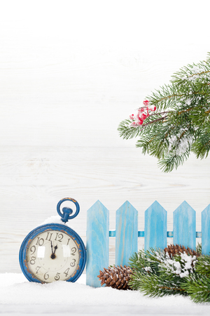 Christmas alarm clock and fir tree branch covered by snow in front of wooden wall. With copy space for your greetings 版權商用圖片