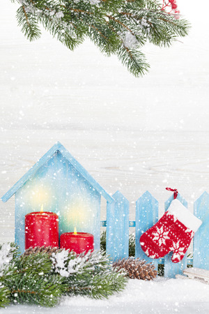Christmas decor, candles and fir tree branch covered by snow in front of wooden wall. Xmas backdrop with space for your greetings