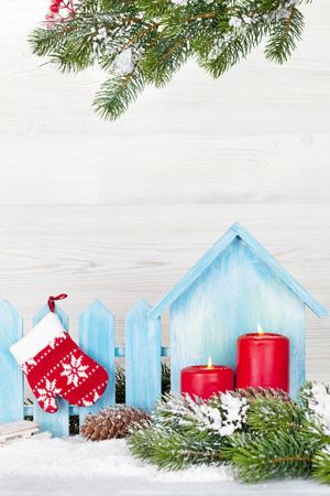 Christmas candles, decor and fir tree branch covered by snow in front of wooden wall. View with copy space 스톡 콘텐츠
