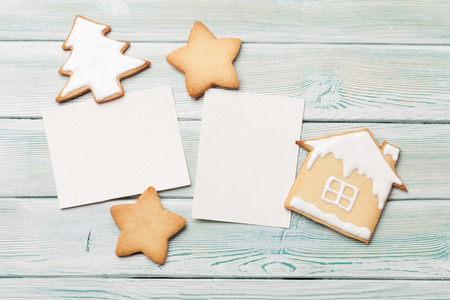 Christmas blank photo frames and gingerbread cookies on wooden background. Top view with space for your greetings. Flat lay