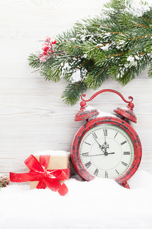 Christmas gift box, alarm clock and fir tree branch covered by snow in front of wooden wall. View with copy space