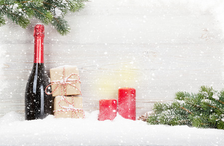 Christmas gift boxes, champagne bottle and xmas fir tree branch. View with space for your greetings