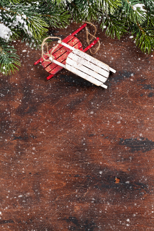 Christmas backdrop with decor and fir tree branch covered by snow oves wooden texture. Xmas background with space for your greetings