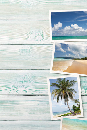 Travel vacation background concept with weekend photos on wooden backdrop. Top view with copy space.
