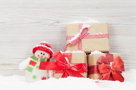 Christmas gift boxes and snowman toy. View with space for your greetings