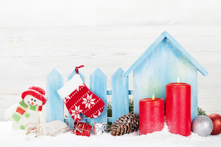 Christmas candles, snowman toy, decor and fir tree branch. Xmas greeting card with space for your greetings Фото со стока