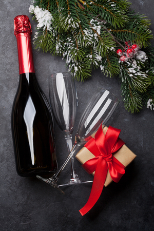 Christmas card with champagne, xmas gift box and fir tree branch covered by snow on stone background. Top view 스톡 콘텐츠